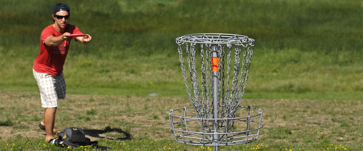 a man in a red t-shirt aims a disc at a disc golf goal.