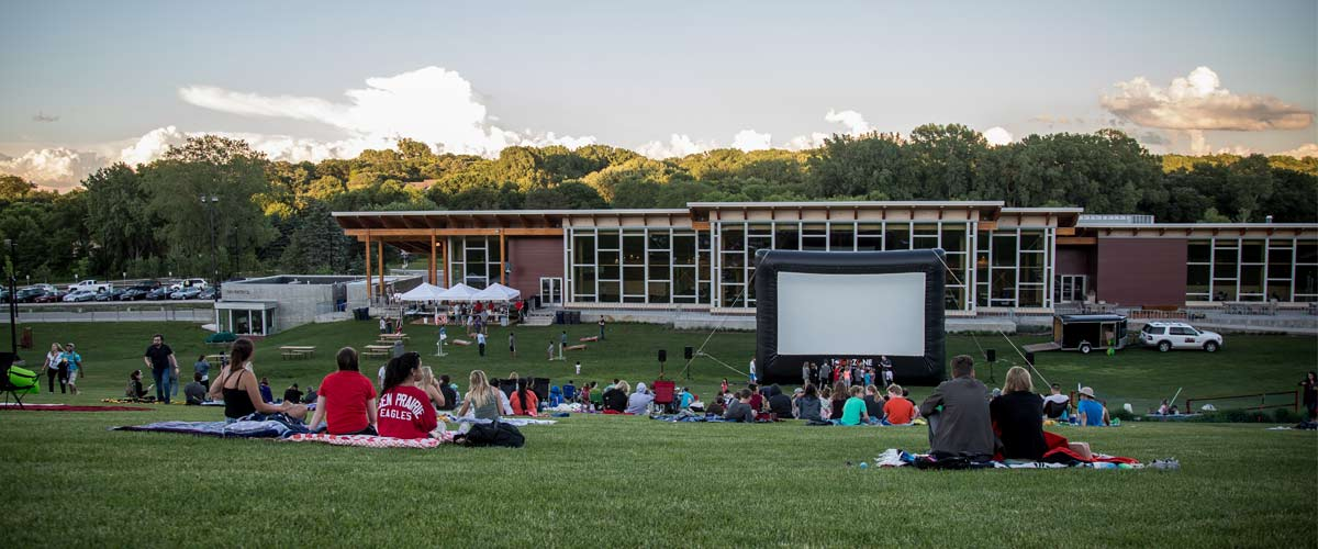 an inflatable movie screen stands in front of a chalet while people sit on a grassy hill to watch a movie.