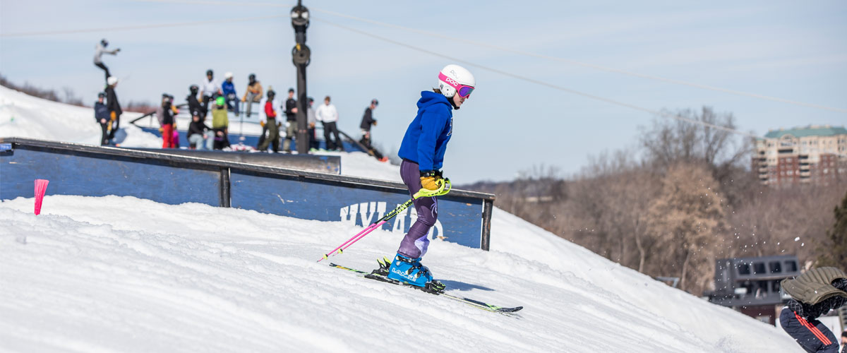 A girl in a white helmet and blue jacket skis down a hill.