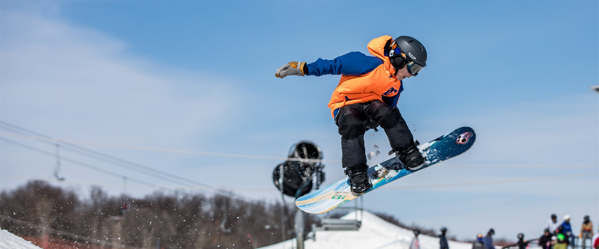 a snowboarder in an orange jacket catches air over the ski hill.