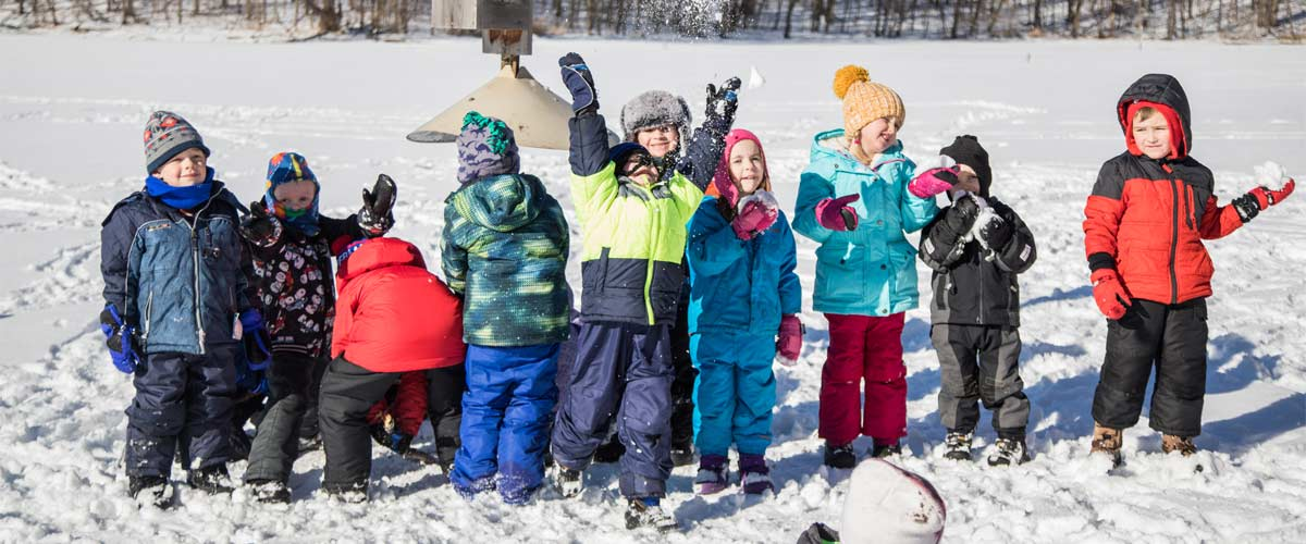 several young children lined up in the snow smiling at the camera. One is throwing snow in the air.