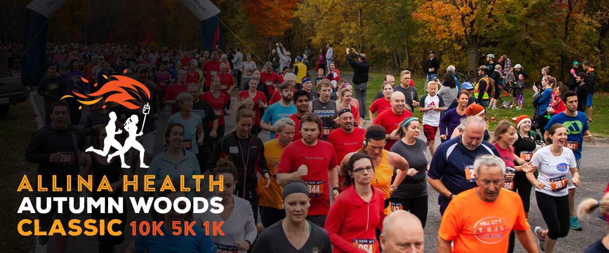 "runners starting the Autumn Woods Classic race. A graphic in the bottom left corner says ""Allina Health Autumn Woods Classic 10K, 5K, 1K."""