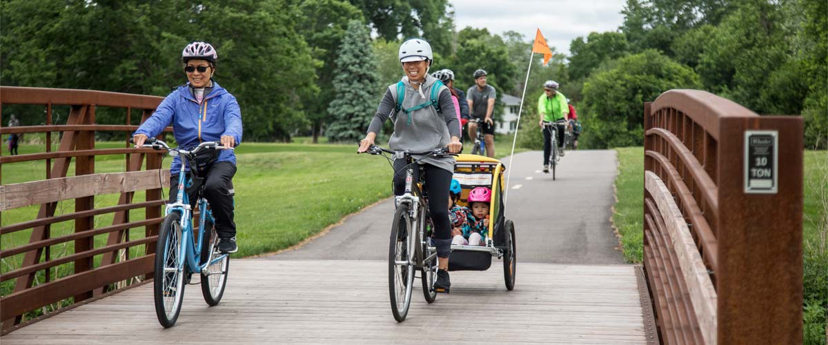 two woman ride bikes over a bridge on a paved trail. One woman is pulling a child trailer.