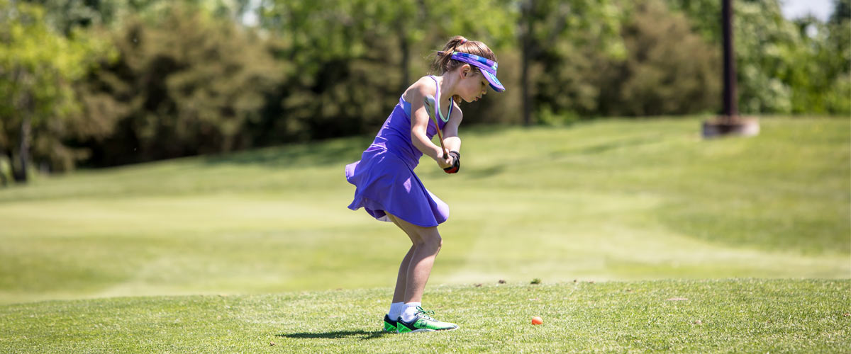 a girl in a purple shirt, skirt and visor swings a golf club.
