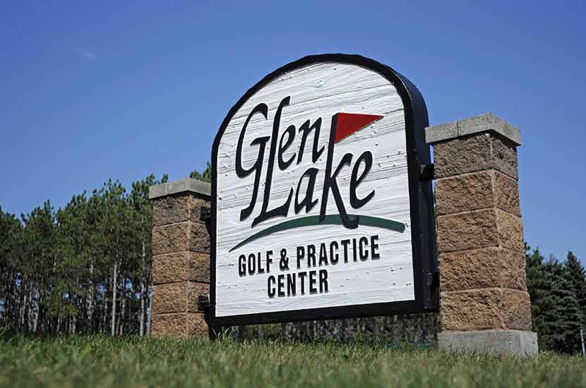 A white sign made of wood and brick says Glen Lake Golf and Practice Center
