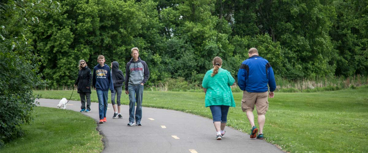 people walk in both directions on a paved trail in the summer.