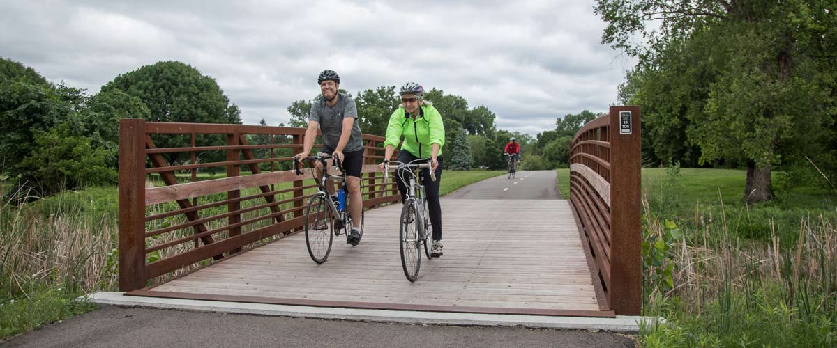 a man in a gray t-shirt and a woman in a neon green jacket ride their bikes over a wooden bridge on a bike path.