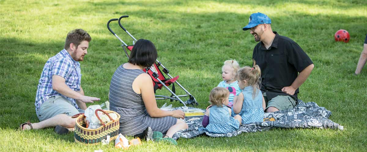 A family picnics in the grass.