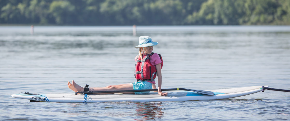 a girl sits on a stand-up paddleboard in the middle of a lake.
