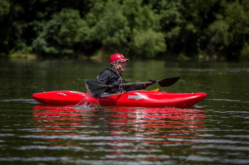 A man in a red hat paddles a red kayak on the water.