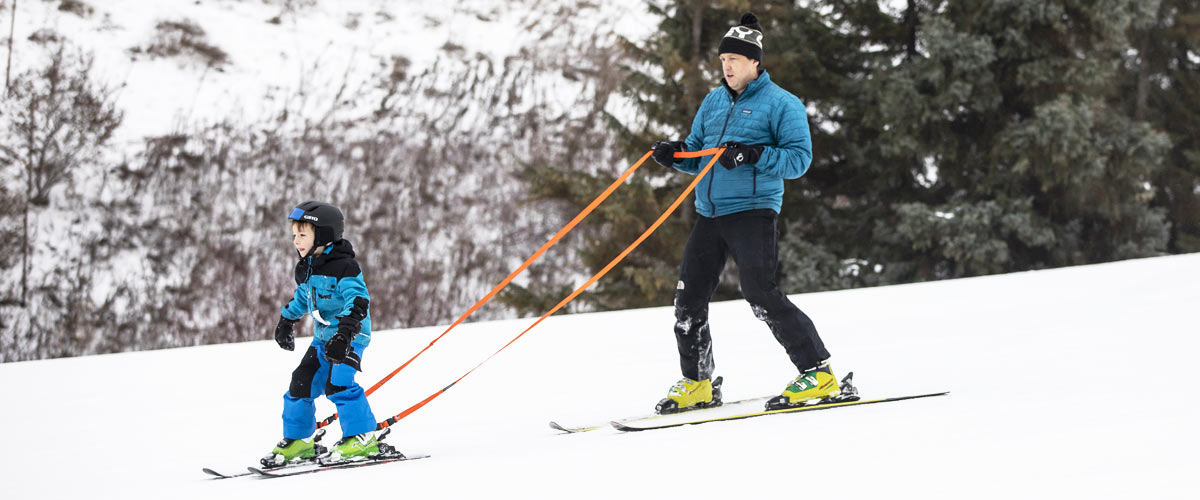 a man in a blue coat helps a boy ski down a hill by holding an orange rope that is strapped to the boy's boots.