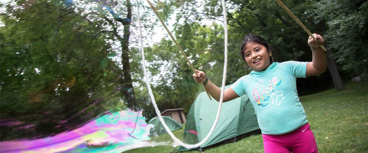 A girl in a teal shirt and pink pants smiles as she makes a giant bubble using sticks and rope.