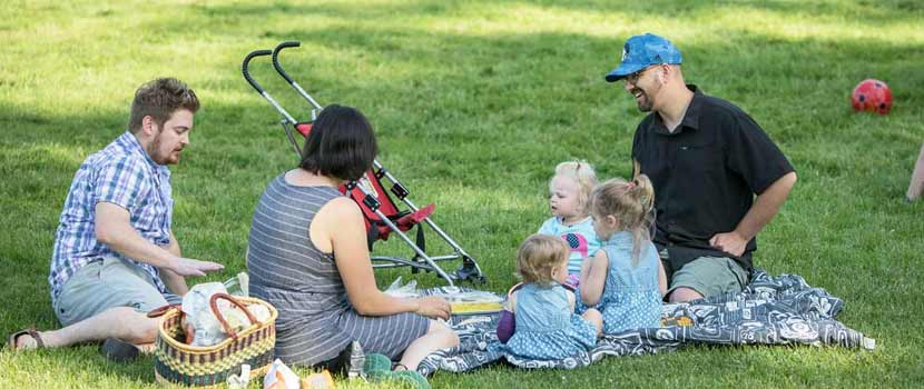 a family with three adults and three small kids has a picnic in the grass.