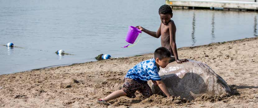 Two boys play with sand toys on a beach.