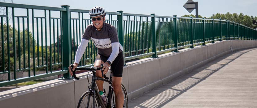 A gives a thumbs up as he bikes over a concrete bridge.