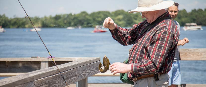 An older man reaches for a fish he caught from a wooden pier.