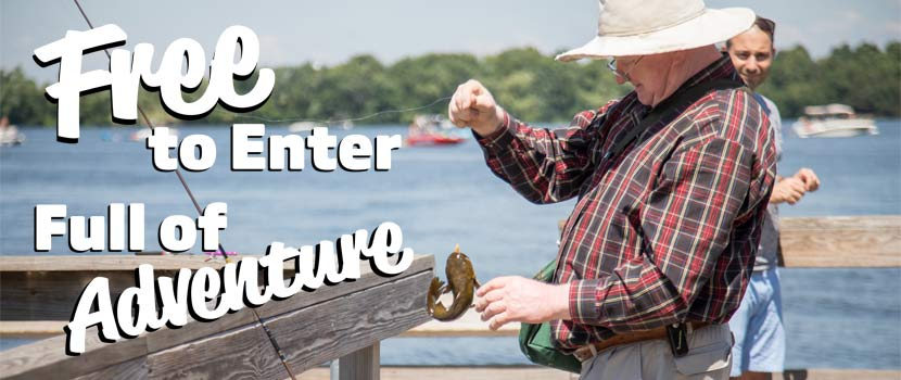 "An older man reaches for a fish he caught from a wooden pier. Text on the left side of the image reads ""Free to Enter, Full of Adventure."""