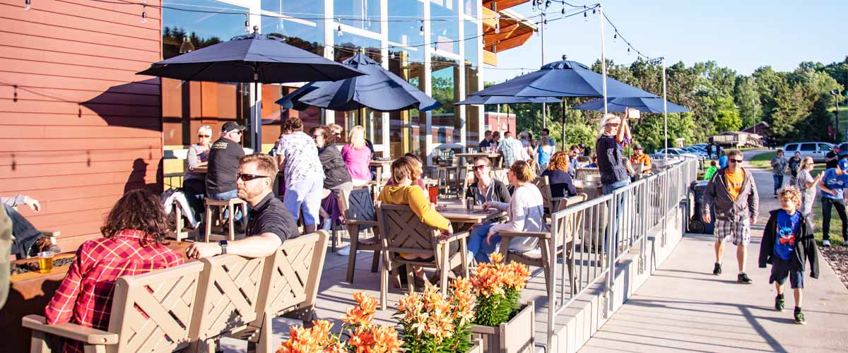 People having happy hour on an outdoor patio on a sunny day.