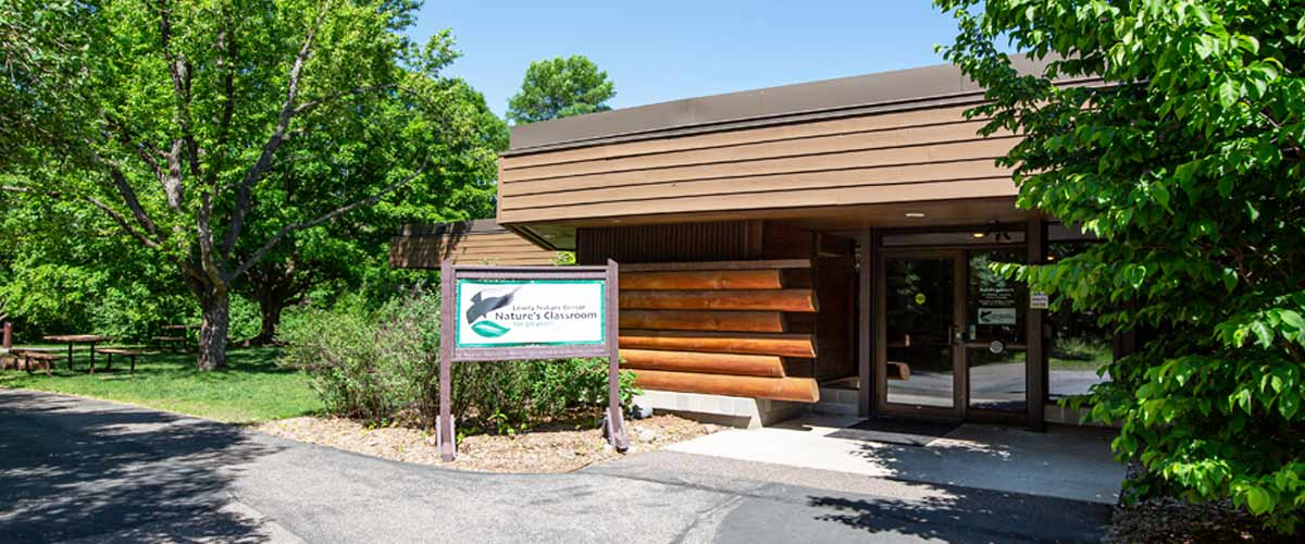 "The outside of a brown building with log features and a sign that says ""nature's classroom for 50 years."""