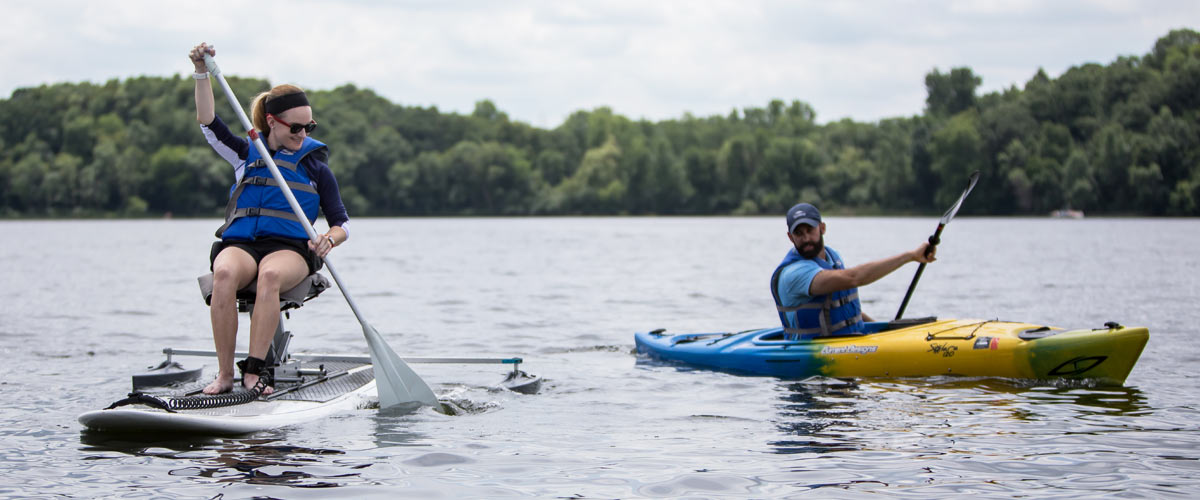 a woman paddles an adapted kayak next to a man in a kayak.