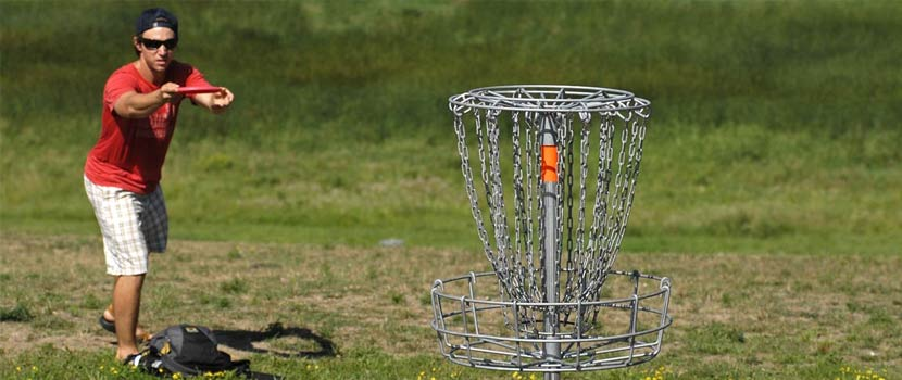 A man aims a disc at a disc golf goal.