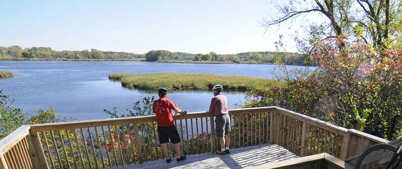 Two men in bike helmets stand on a wooden overlook near a lake.