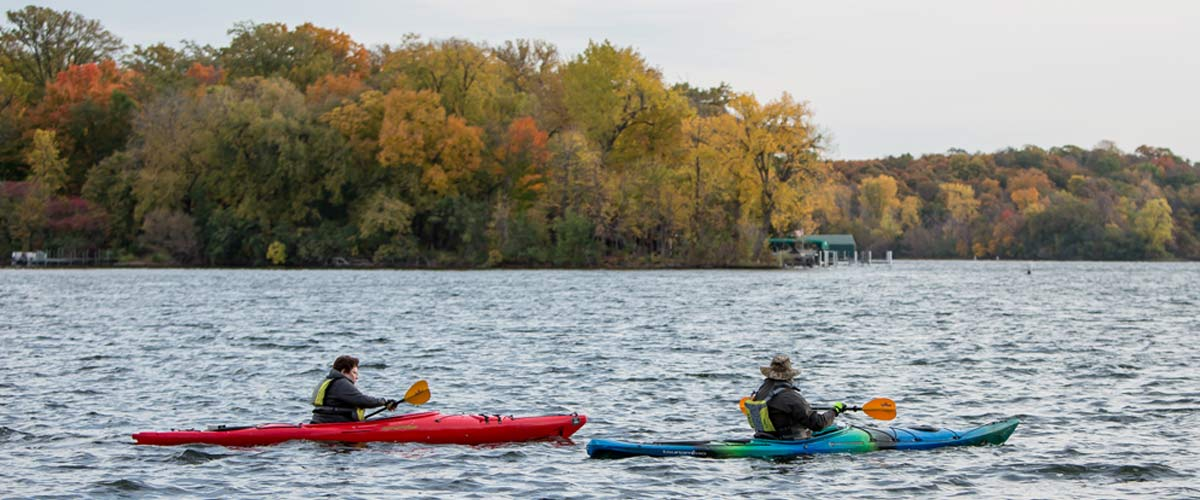 Two kayakers paddle on a lake. Behind them, the shore is lined with trees that have changed color in the fall