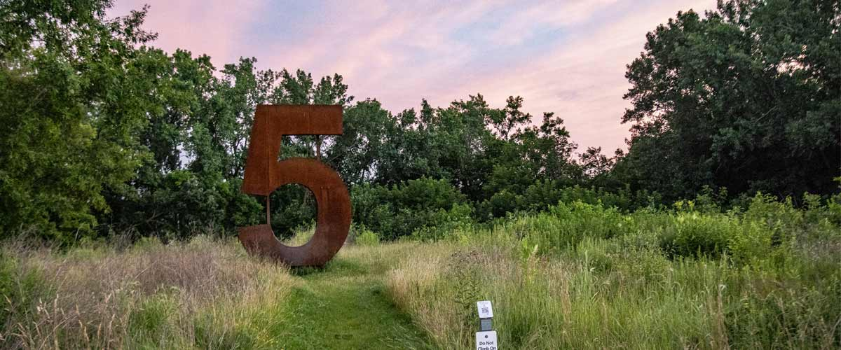 A giant metal number 5 sculpture in the grass with a sunset behind it.