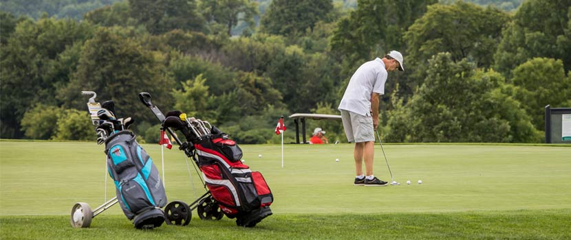 A man golfs on a course. Two golf bags are in the foreground.