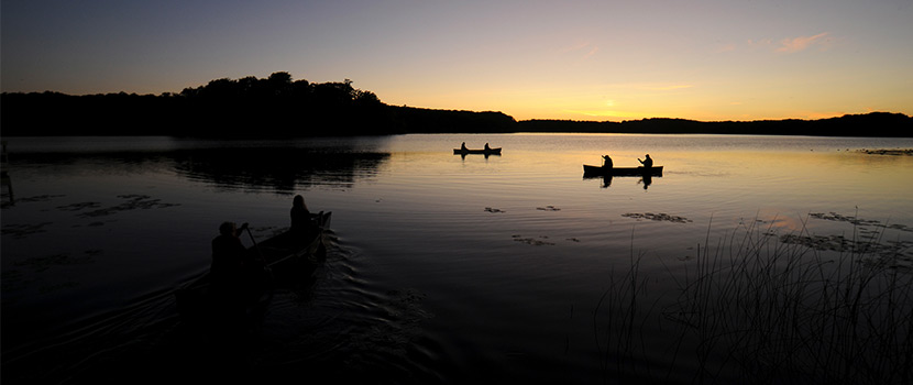 three canoes paddling on a lake just after sunset