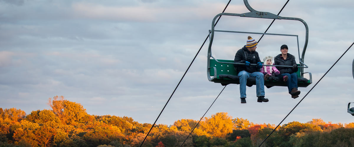A couple rides a chairlift over trees that have turned orange in the fall.
