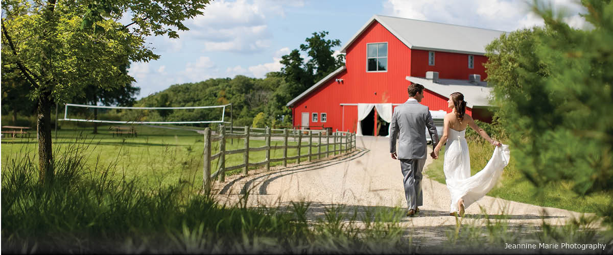 A bride and groom walk toward a red barn.