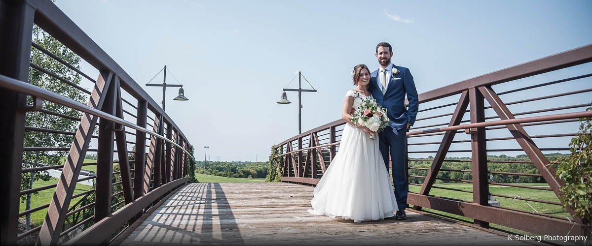 A bride and groom pose on a bridge on a sunny day.
