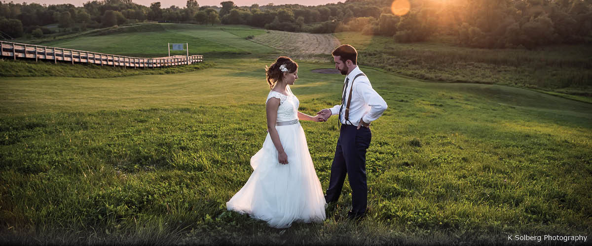A bride and groom pose for a photo in the grass at sunset.
