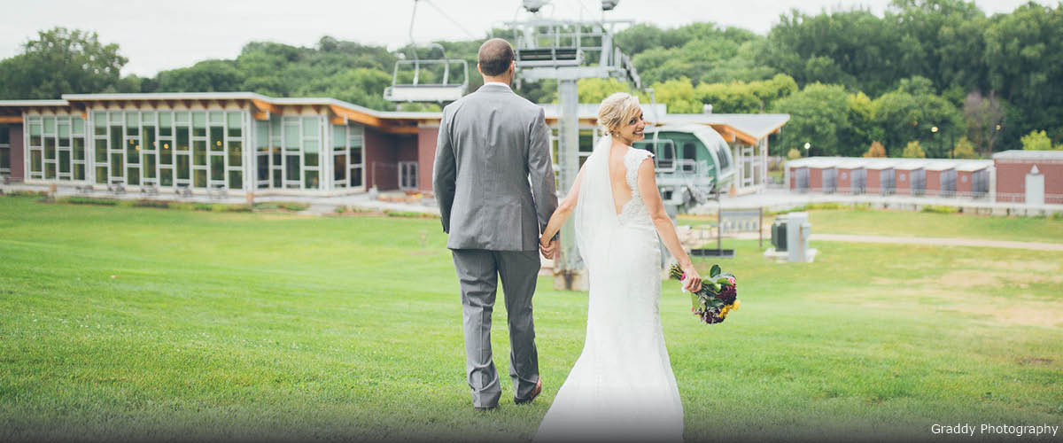 A bride and groom walk down a ski hill in the summer. You can see chairlifts and a chalet in the background.