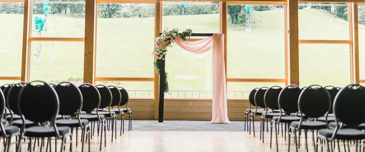 A room with tall windows set up for a ceremony.