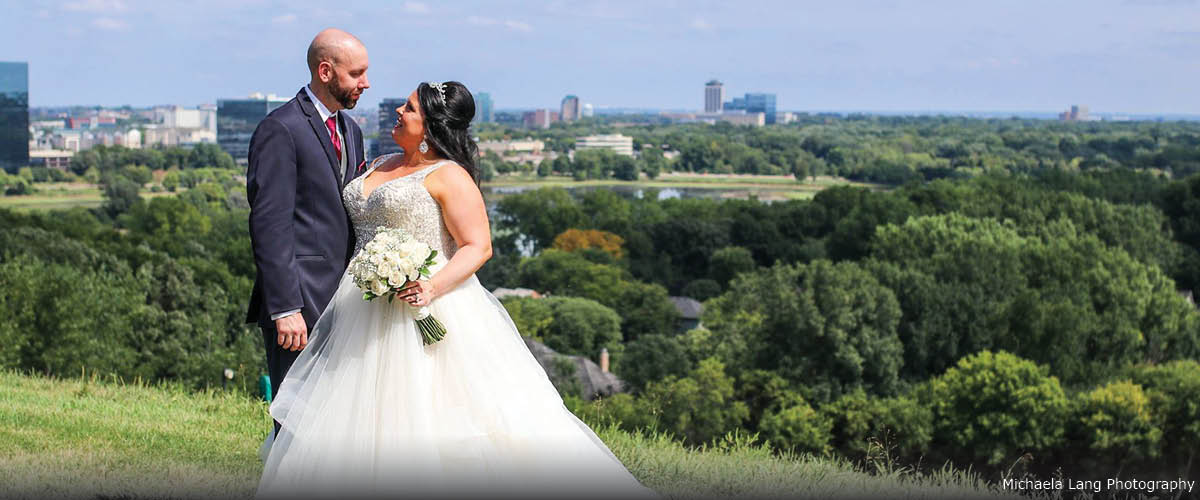 A bride and groom pose at the top of a hill. You can see a cityscape in the distance.