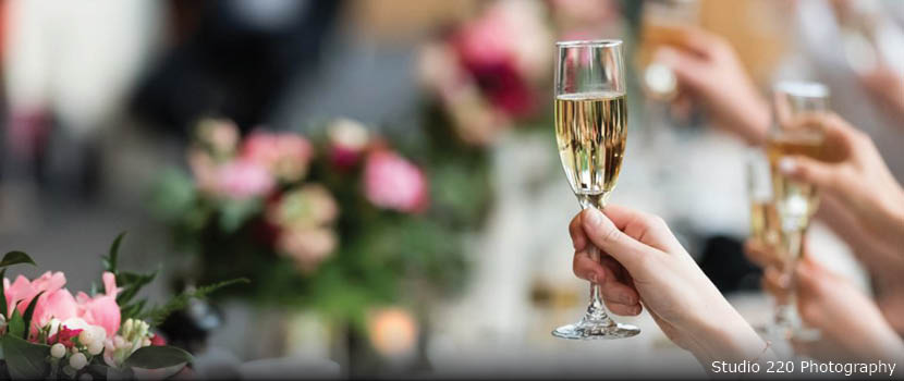A hand holds up a glass of champagne over a head table at a wedding.