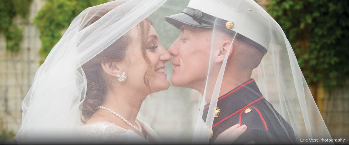 A bride and military groom kiss under her veil.