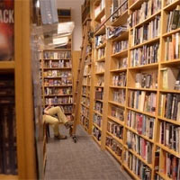 A person's legs stick out in the aisle at a bookstore.