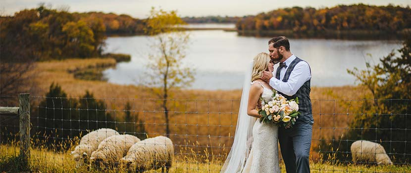 bride and groom on a fall hillside overlooking a lake