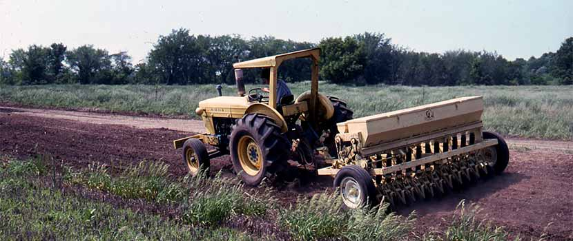 1970s tractor seed drill planting on the prairie