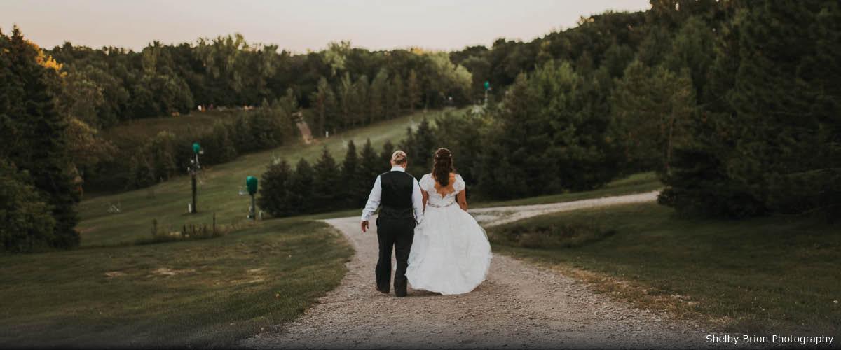 Two brides hold hands as they walk down a dirt trail. Ahead of them are large hills, pine trees and a chairlift.