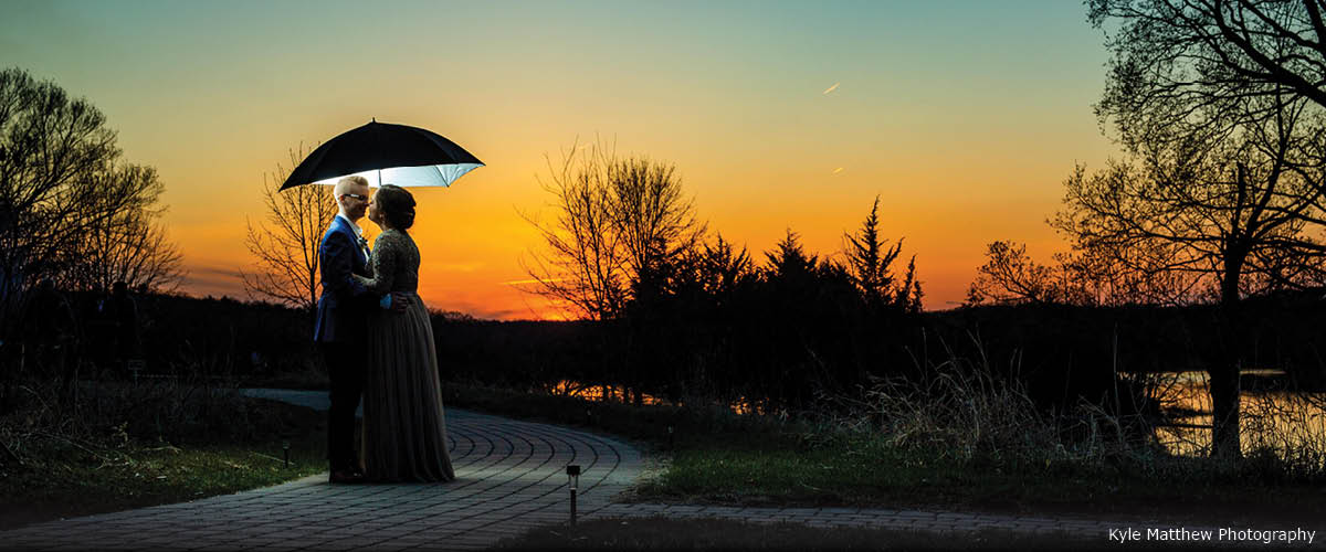 A couple poses at sunset under an umbrella.