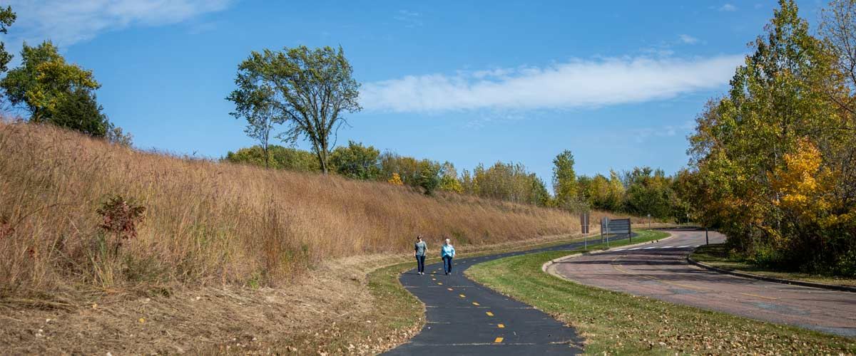 Two people walk down a paved path in an open, grassy area in the fall.