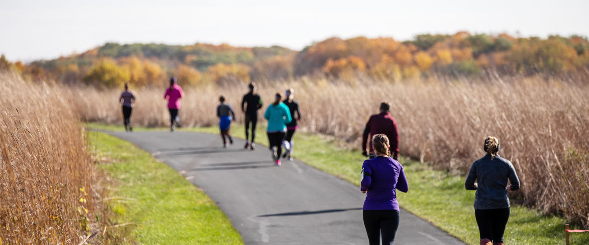 Several people run on a paved path through tall, tan prairie grasses. In the distance, you can see a tree line changing color with the fall season.