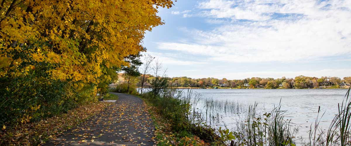 A paved trail winds past a lake in the fall.