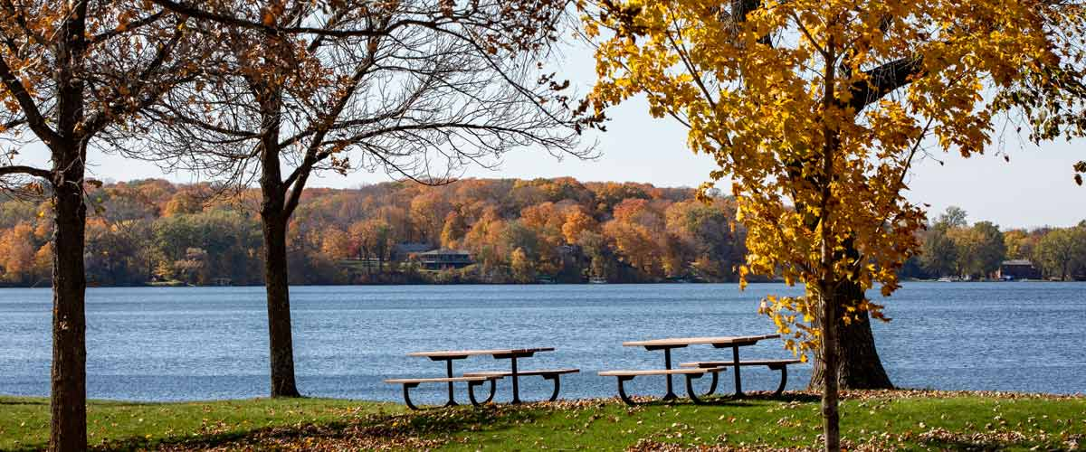 Two picnic tables overlook a lake in the fall/