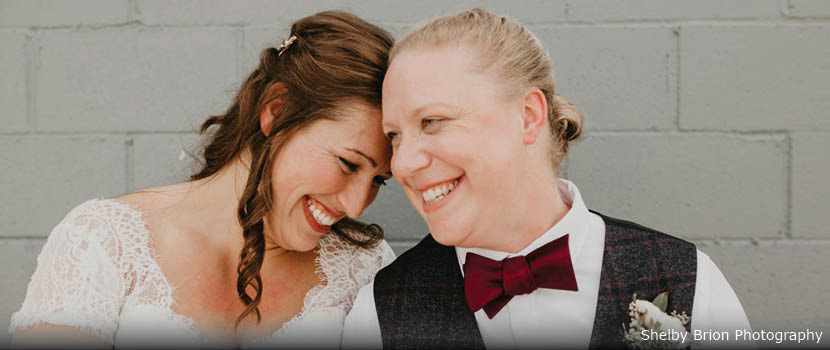 Two brides smile as they lean their foreheads against each other.