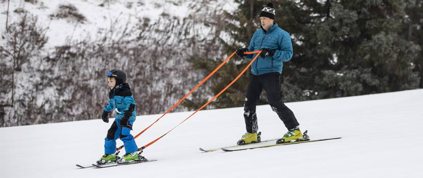A man teaches a boy how to downhill ski.